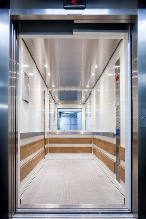 Moderne Aufzugkabine mit Edelstahl und Holz